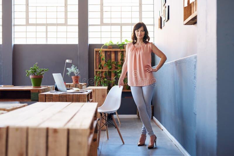 单独站立在一个现代办公室的确信的年轻女实业家 库存图片