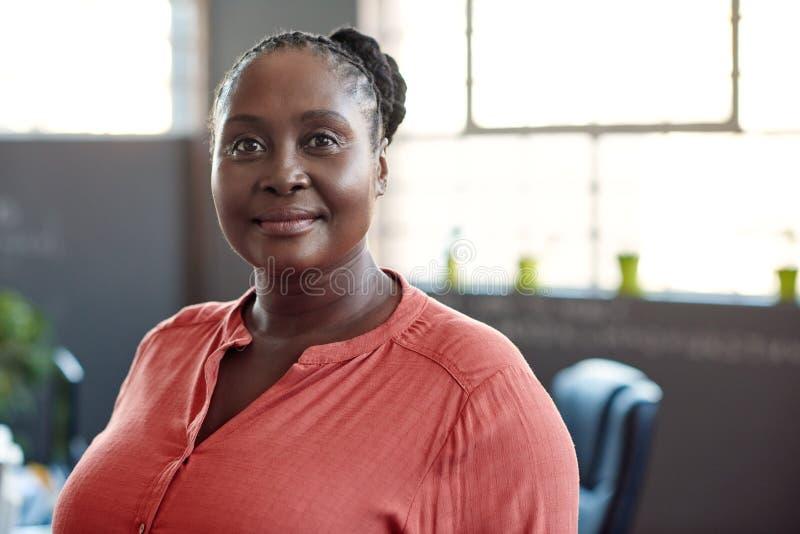 单独站立在办公室的确信的年轻非洲女实业家 免版税图库摄影