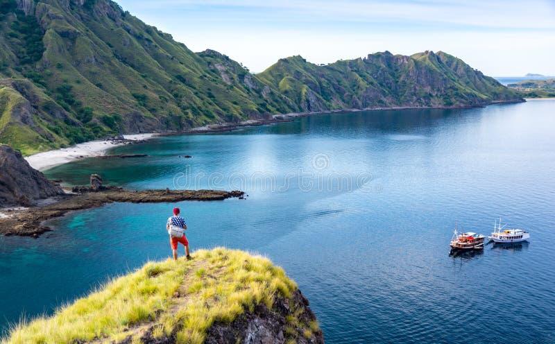 单独站立在峭壁山的年轻远足者 库存图片