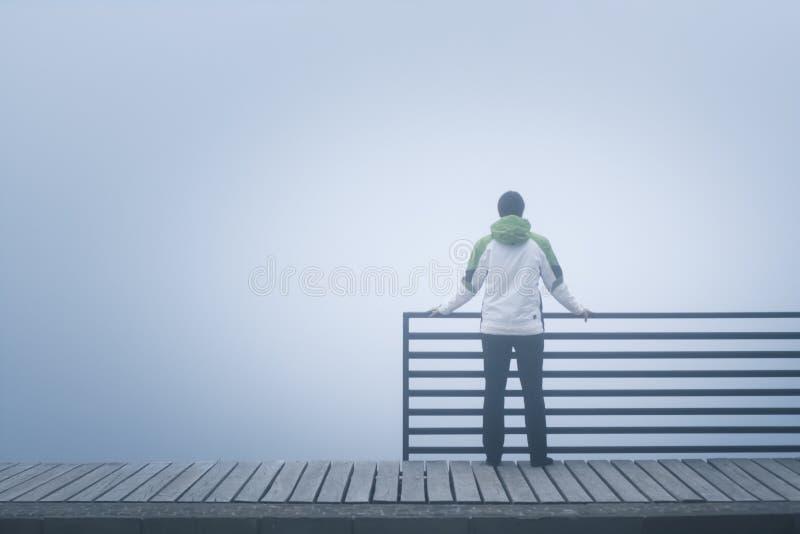 单独站立在桥梁的孤独的妇女,失去在想法在一有雾的天 库存照片