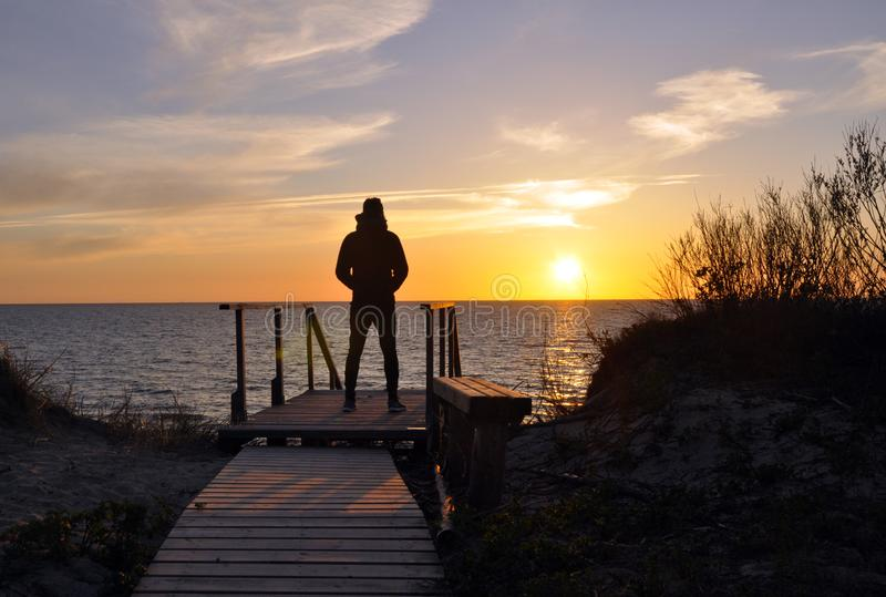 单独站立在海滩的人剪影 库存照片
