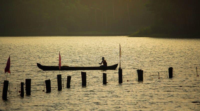 单独老人剪影小船的 免版税库存照片