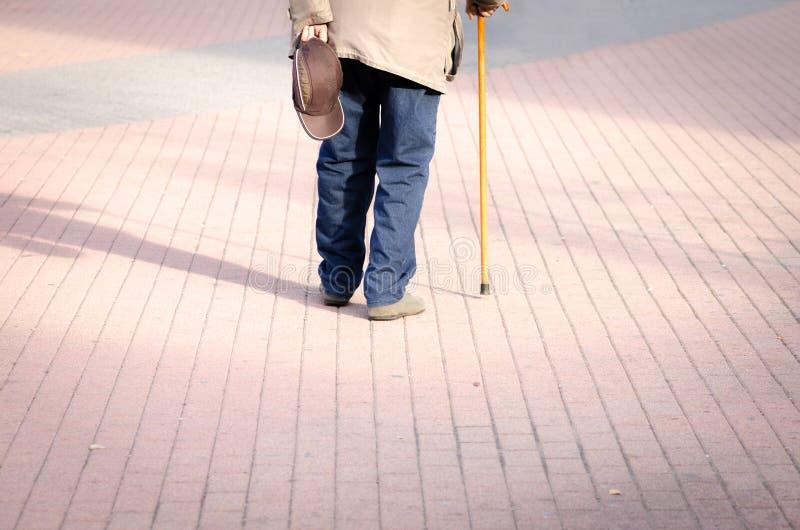 单独老沮丧的人步行在街道下有从后面的拐棍或藤茎感觉偏僻和失去的视图 库存图片