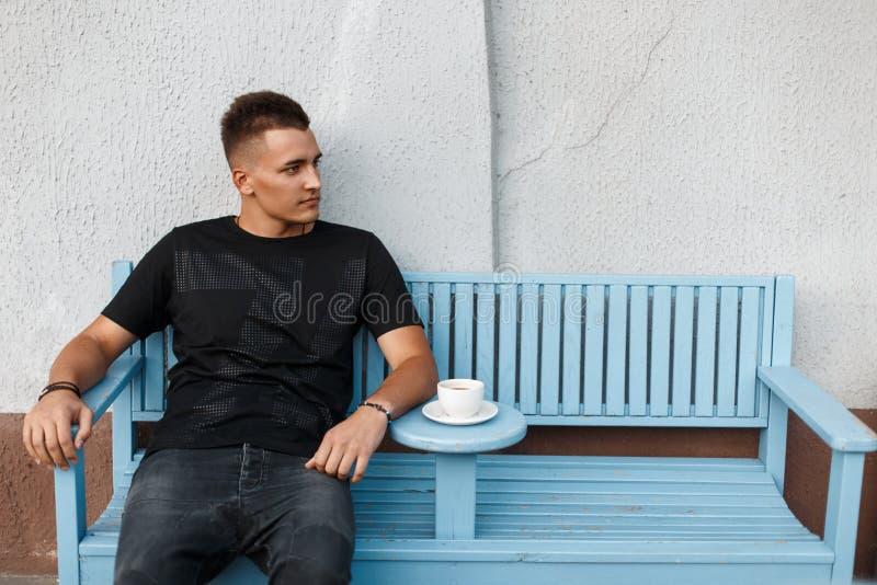 单独英俊的哀伤的人长凳和饮料咖啡的 库存图片