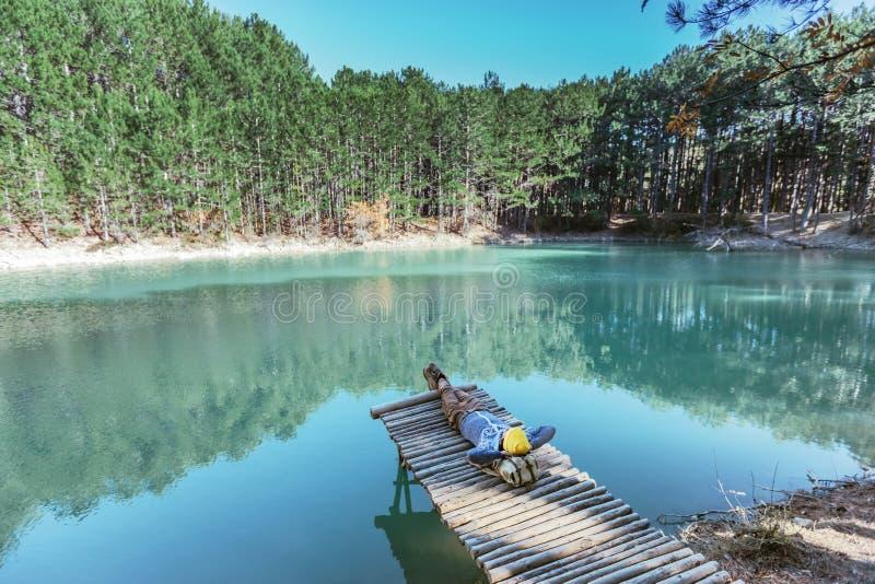 单独走到蓝色湖的人旅客在森林 图库摄影