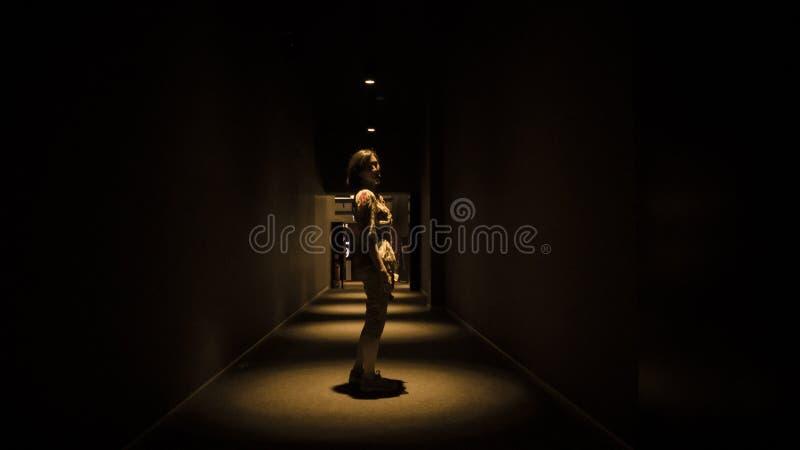 单独走在公寓的一个空的黑暗的走廊的妇女在与拷贝空间的透视图 免版税图库摄影