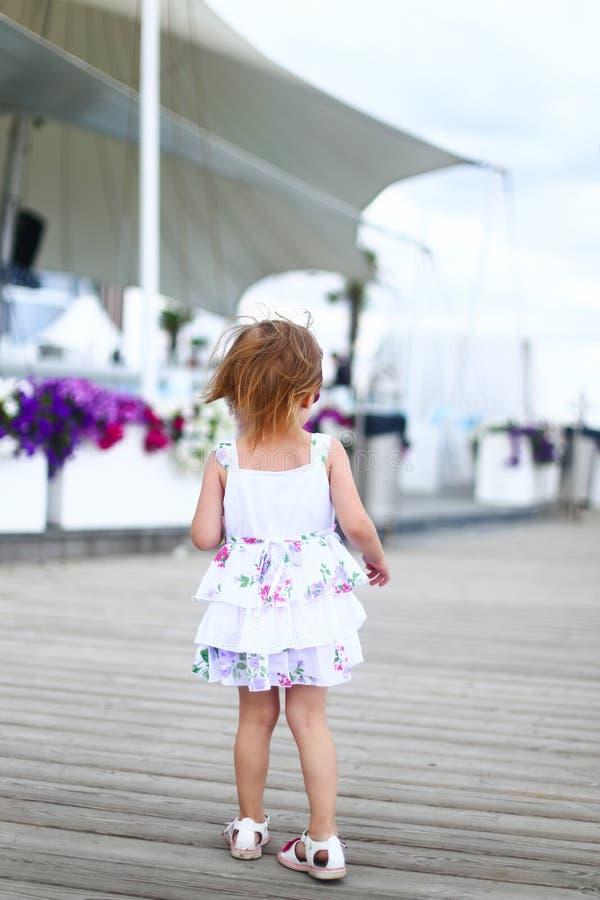 单独走在夏天的小的女孩佩带的礼服 库存图片