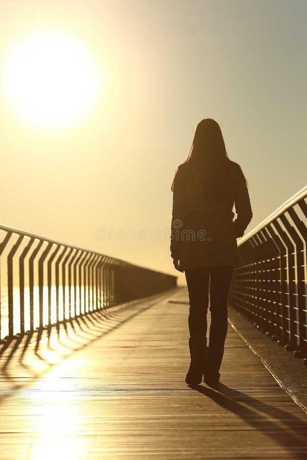单独走在日落的哀伤的妇女剪影 免版税库存照片