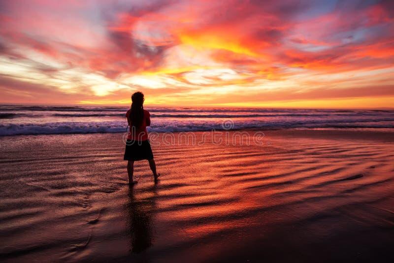 单独走在日落的海滩的妇女 库存图片
