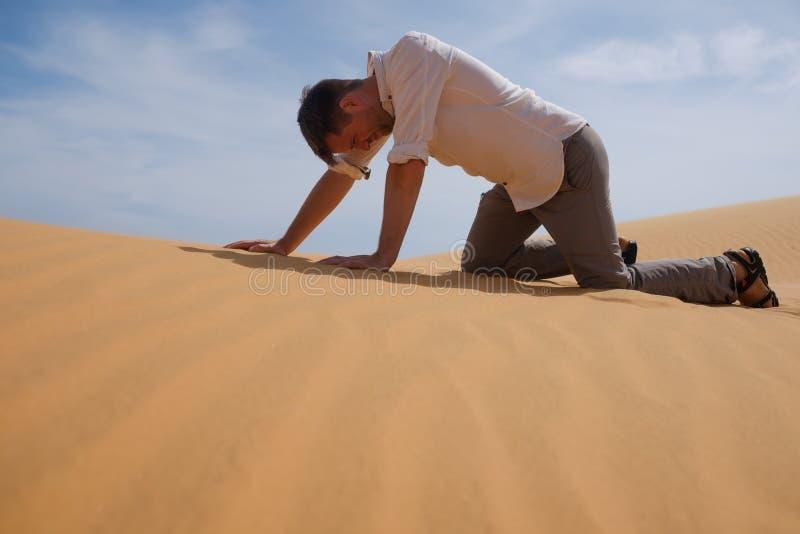 单独走在晴朗的沙漠的人 他丢失和喘着气 没有水和能量 库存照片