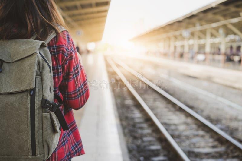 单独走在有背包的火车站平台的年轻亚裔妇女背包徒步旅行者旅客 免版税库存图片