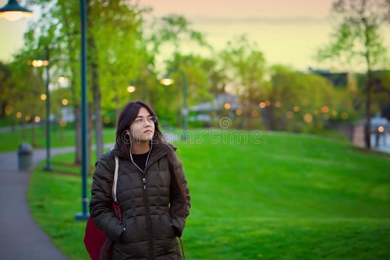 单独走在湖公园的年轻两种人种的妇女在黄昏 免版税库存图片