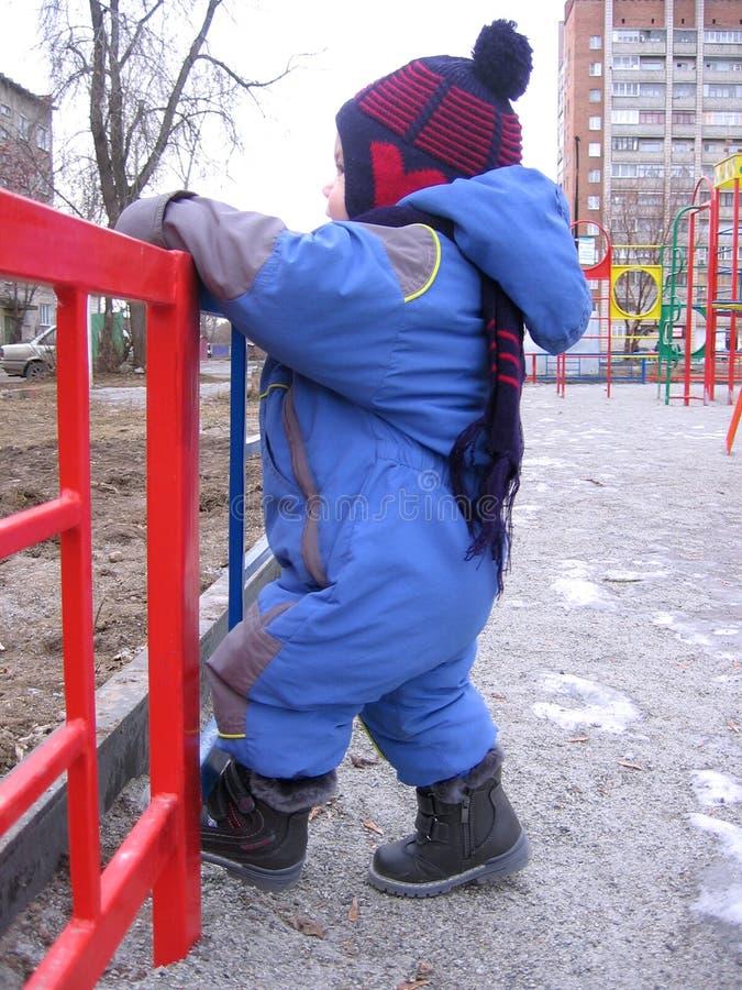 单独走在秋天攀登的街道上的小男婴在篱芭 免版税库存图片