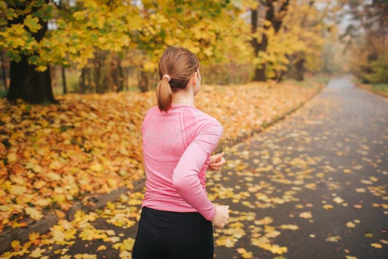 单独跑步在公园的年轻女人 这是秋天外面 她在路跑 库存照片