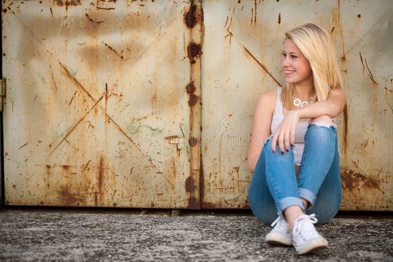 单独年轻白肤金发的白种人女孩在街道上 库存图片