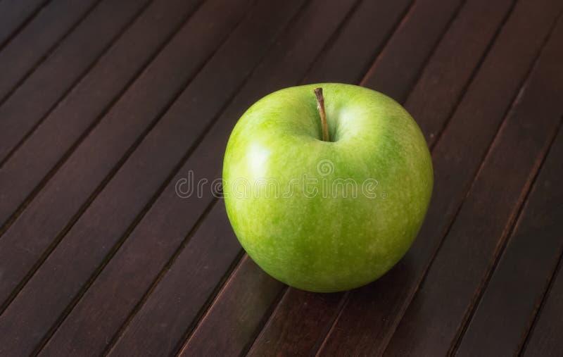单独绿色苹果计算机太木桌 库存图片