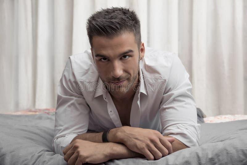 单独说谎在他的床上的性感的男性模型 图库摄影