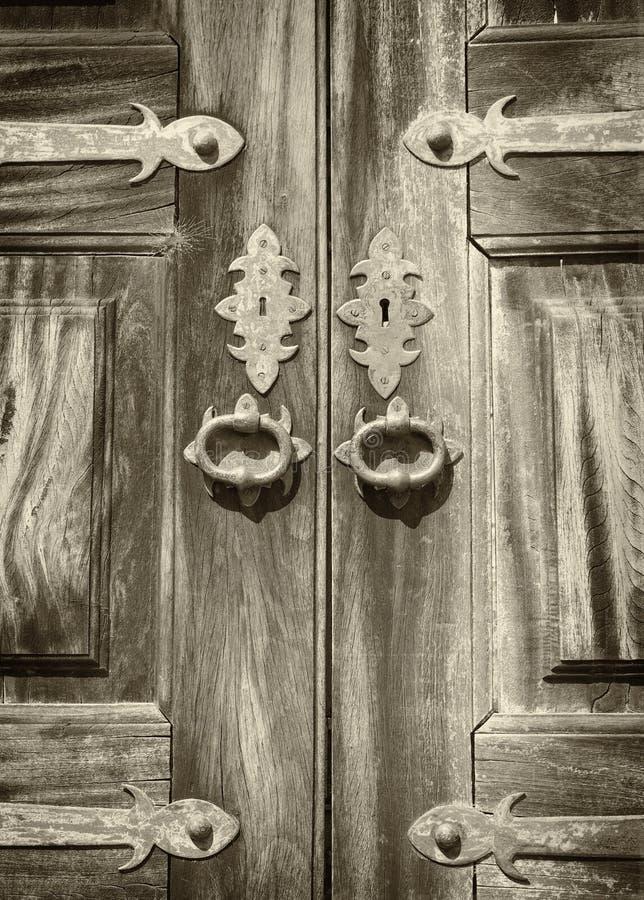 单色乌贼属关闭与华丽金属装饰匙孔和把柄的古老被涂清漆的木双门 免版税图库摄影