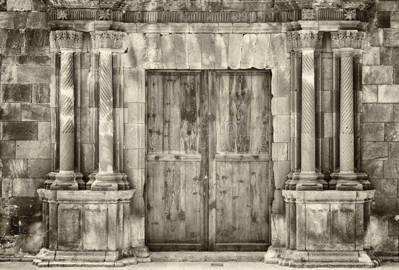 单色在一个老石大厦的乌贼属古老木双门与粉碎围拢入口的华丽专栏 库存图片