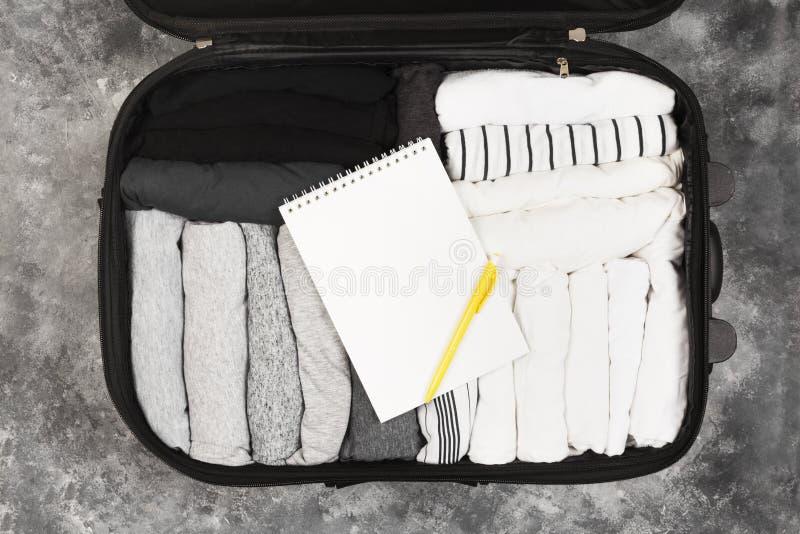 单色衣裳包装在黑手提箱的 装箱单 免版税库存图片