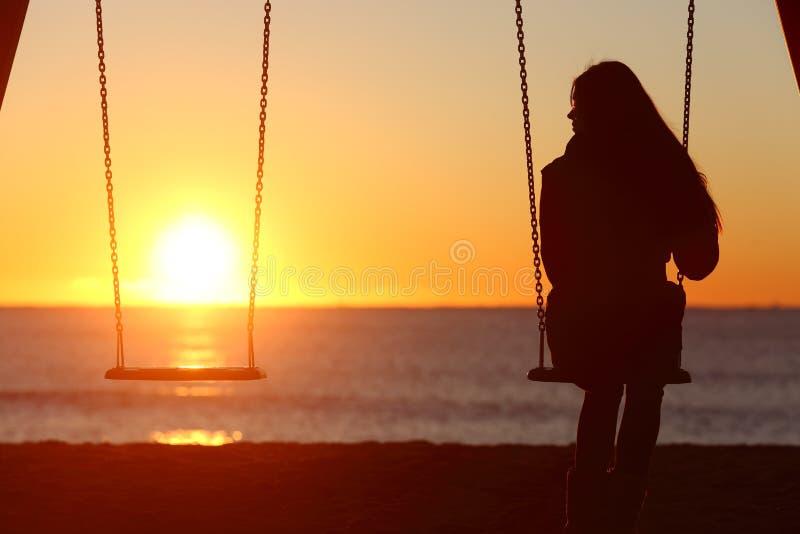 单身妇女单独摇摆在海滩 免版税库存照片