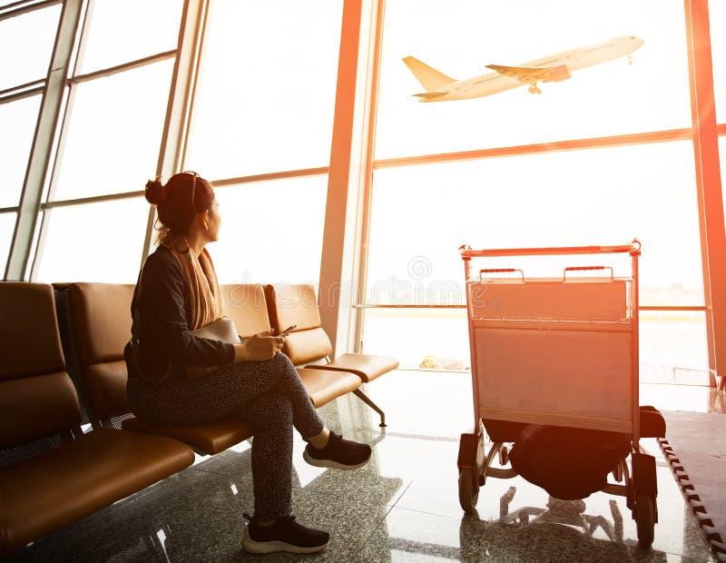 单身妇女坐在机场终端的和passanger飞机飞行 库存图片
