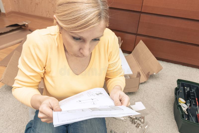 单身新的家具和读指示年轻女人聚集的片断,有家具细节的开放箱子在 库存照片