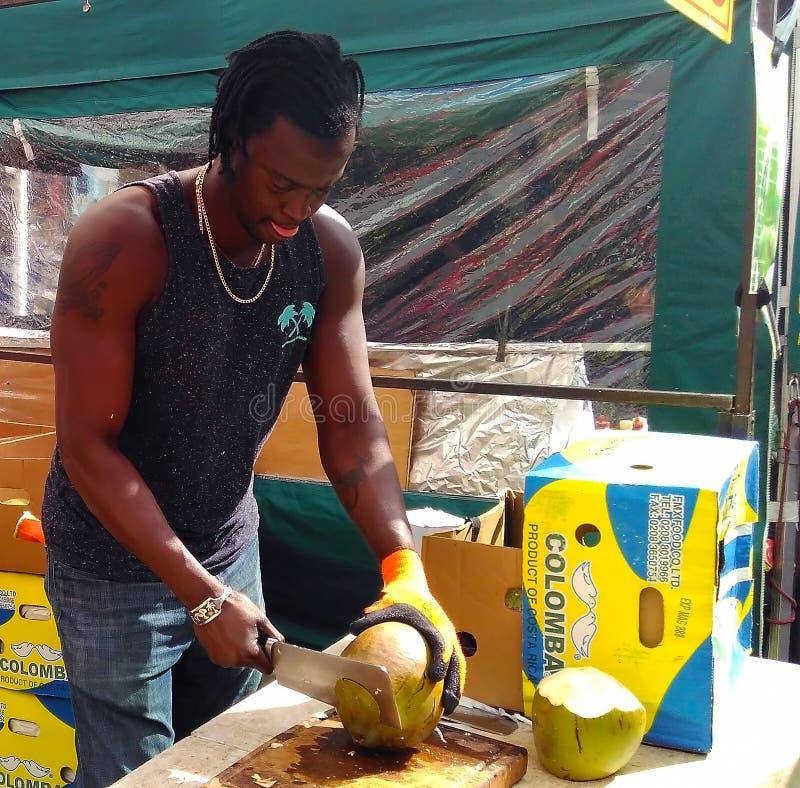 卖主分裂的椰子在跳蚤市场上 库存图片
