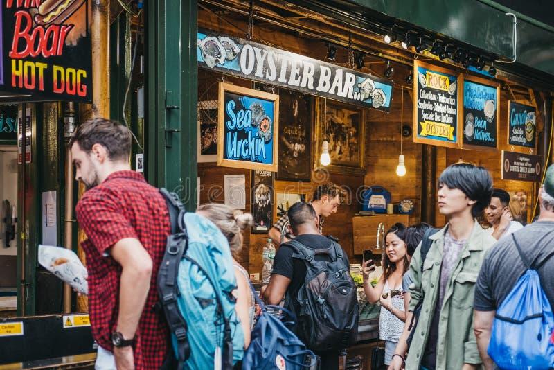 卖主和顾客牡蛎酒吧的在自治市镇市场,伦敦,英国上 免版税库存图片
