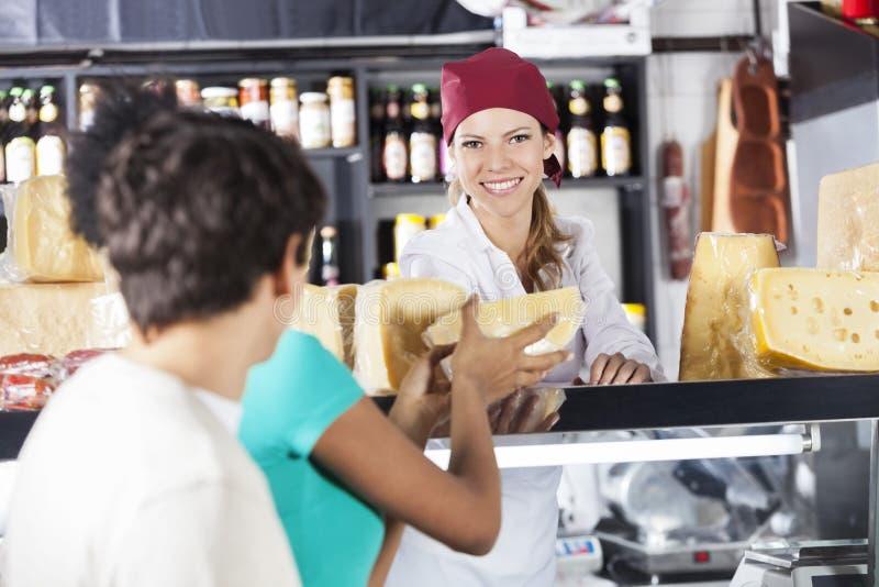 卖乳酪的愉快的女推销员对年轻夫妇 免版税库存照片