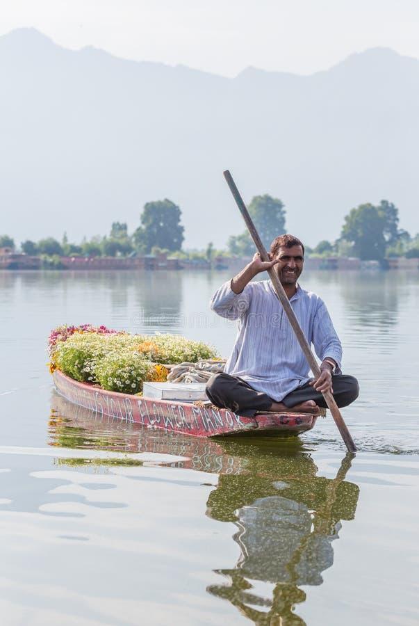 卖从他的小船的未认出的克什米尔人人花在Dal湖在斯利那加,查谟和克什米尔,印度 免版税库存图片