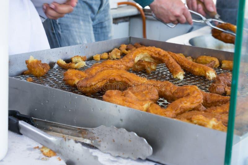 卖传统西班牙点心酥皮点心的供营商油炸Churros在农夫市场上 街道食物 全国烹调 证实 库存照片