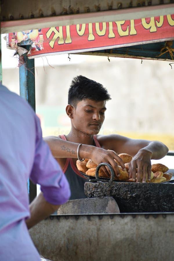 卖印地安快餐kachori的男孩 免版税库存照片
