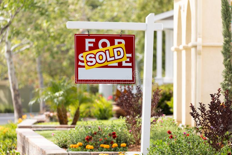 卖在家为销售在新房前面的房地产标志 图库摄影