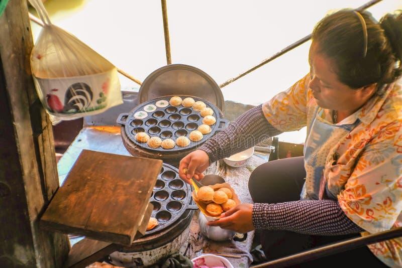 卖在小船的不知道泰国人泰国著名街道食物椰子蛋糕在attaya浮动市场上 春武里市泰国 免版税库存图片