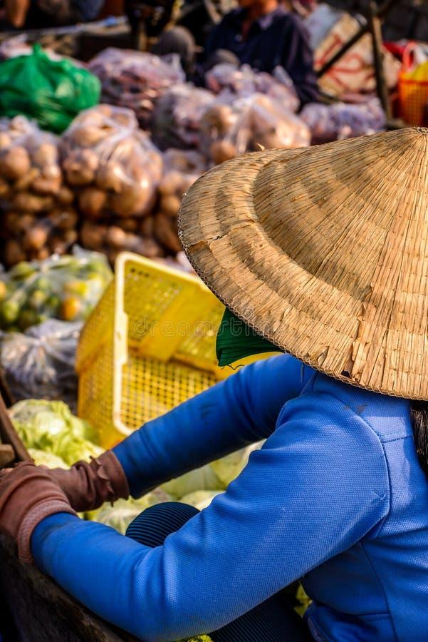 卖在浮动市场上的妇女菜在小船,湄公河,竞争 免版税库存图片