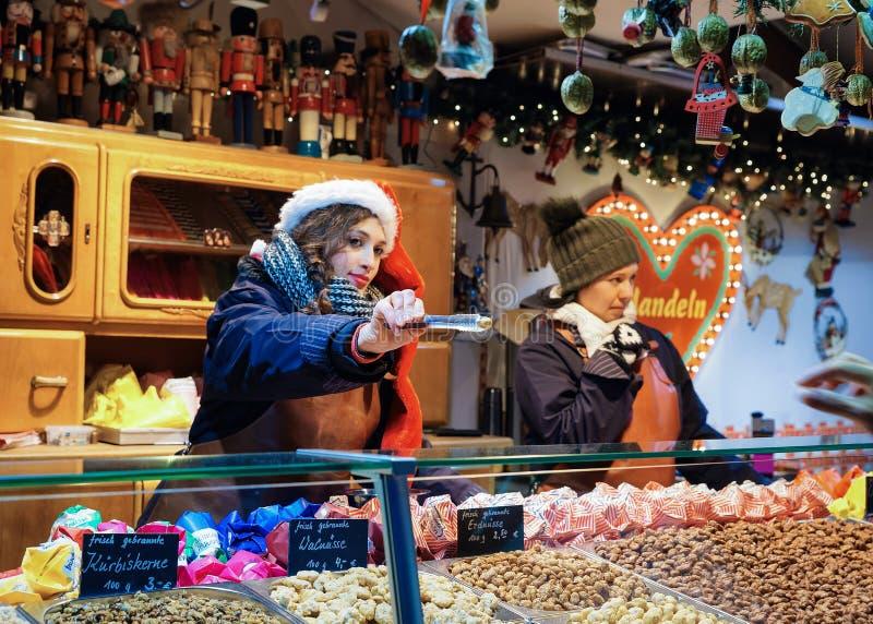 卖坚果的女孩在夜圣诞节集镇霍尔柏林 免版税图库摄影