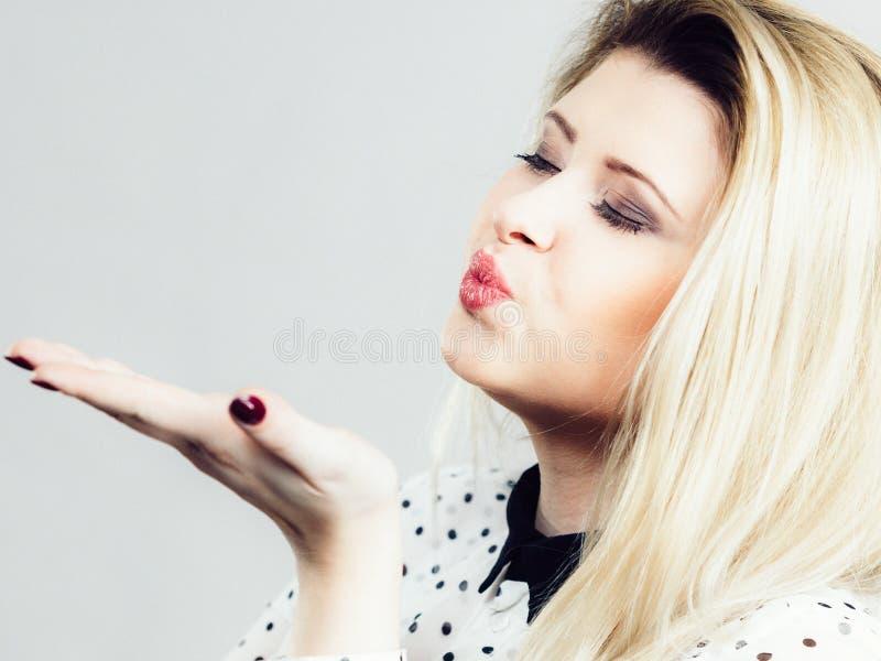 卖弄风情送空气亲吻的白肤金发的妇女 库存图片