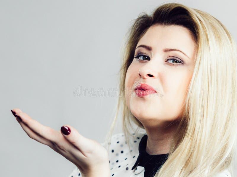 卖弄风情送空气亲吻的白肤金发的妇女 图库摄影