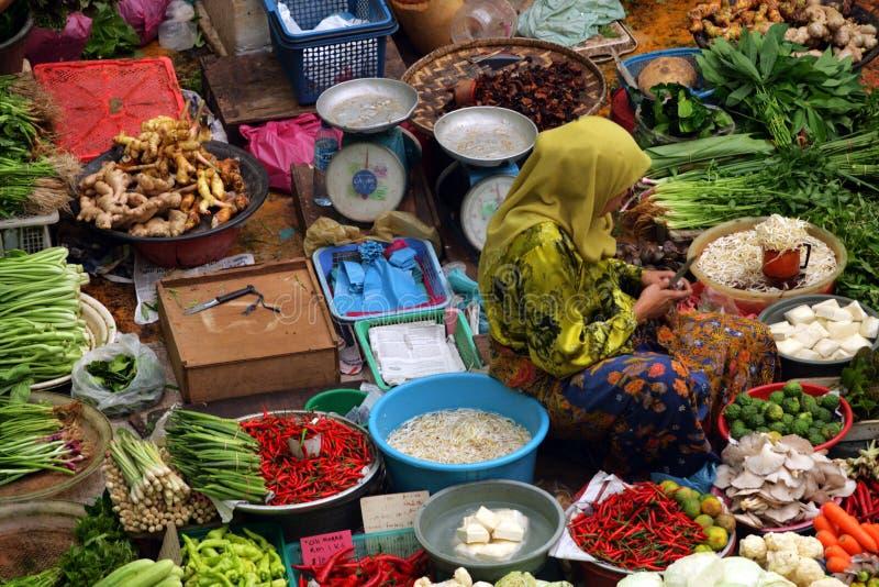 卖新鲜蔬菜的回教妇女在市场上在马来西亚 免版税库存图片