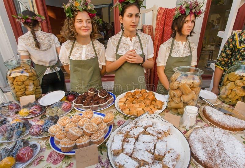 卖曲奇饼、蛋糕和饼的逗人喜爱的女孩在第比利斯的一个地方街道节日期间 库存照片