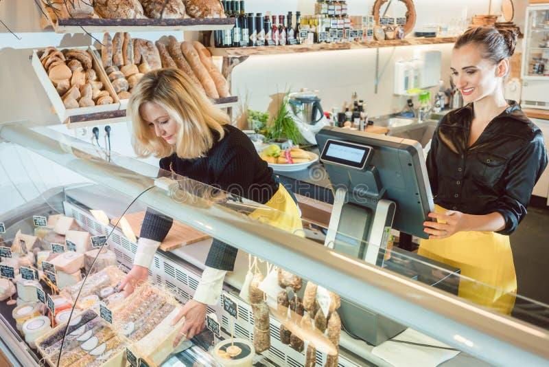 卖杂货的两位女推销员在熟食店 图库摄影