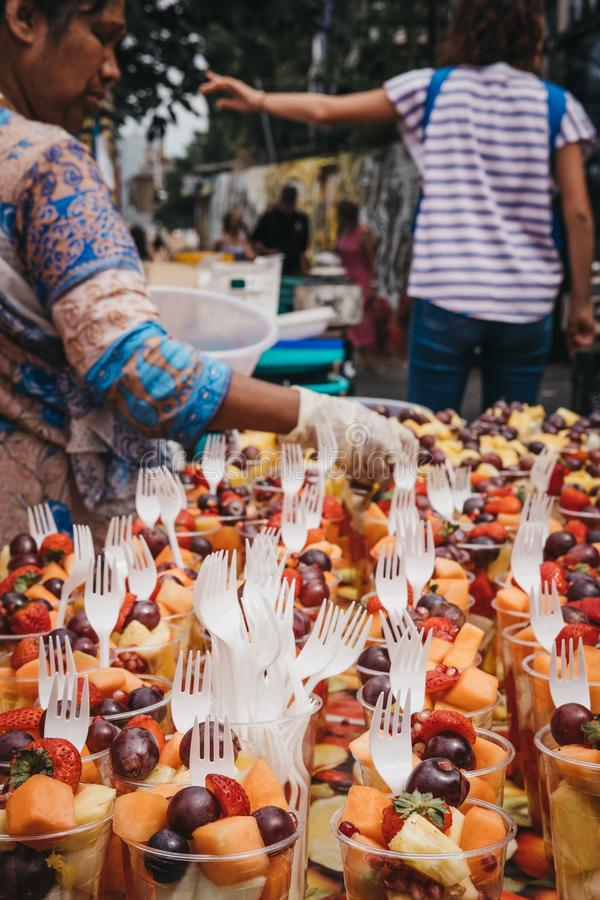 卖杯子在砖车道,伦敦,英国的新鲜水果的妇女 免版税图库摄影