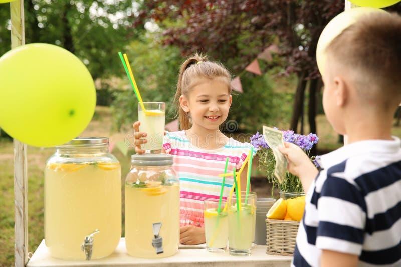 卖柠檬水的小女孩在停留演出地在公园 图库摄影