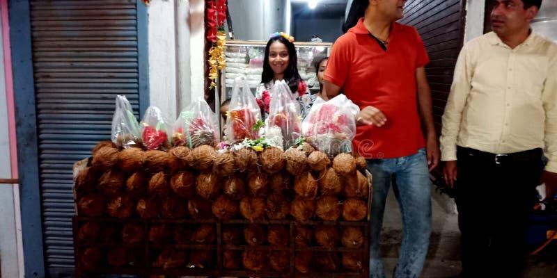 卖椰子的一美丽的印度女孩在寺庙街道 免版税库存照片