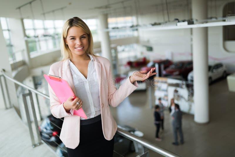 卖汽车的专业推销员在经销权对买家 免版税库存照片