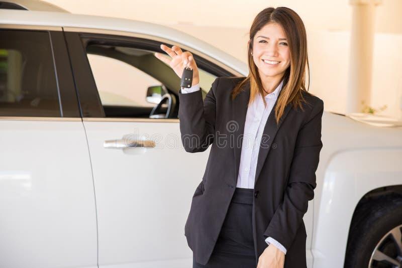 卖汽车的少妇在经销权 库存照片