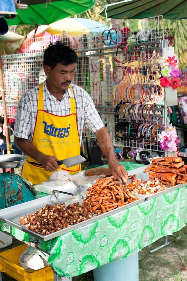 卖油煎的猪肉的泰国人在市场上 普吉岛泰国 免版税库存照片