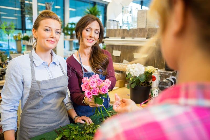 卖罗斯花束的卖花人对顾客在商店 免版税库存照片