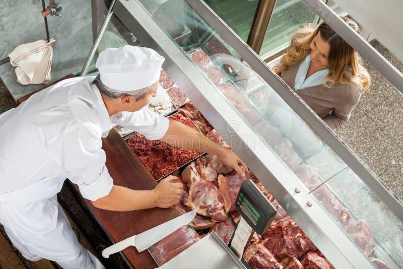 卖肉的屠户对顾客在显示 免版税库存照片